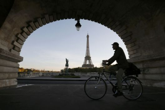A man takes an early morning bicycle ride across a bridge near the Eiffel Tower in Paris