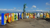 An ancient public sculpture flanked by the city's name, decorated with images from famous local artist Manuel Lepe.
