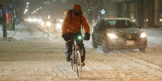 Cyclist commutes in snow on Richmond Street.